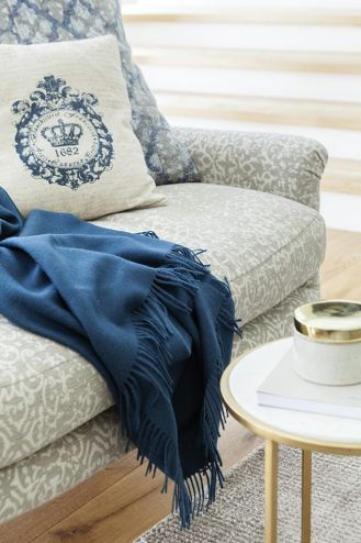 Niebieski i seledynowy pled oraz talerze, miski, szklanki na stole – BB Home, ceramiczne naczynie na stole ze złotą
