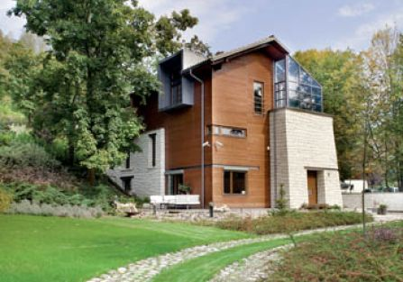 Dom jest nowoczesny, awangardowy, ale zbudowany z tradycyjnych materiałów - ceglana dachówka, ściany z wapiennego