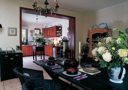 Kuchnia i jadalnia, choć urządzone w różnych stylach, są spójne. W jadalni stoją serwantki z jasnego drewna, nawiązujące do