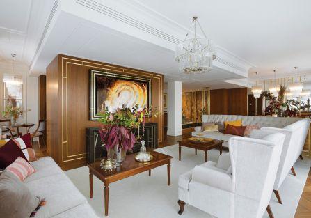 Do orzechowego drewna na podłodze i ścianach architekci wybrali kremowe sofy i dywany, dzięki czemu salon jest lżejszy i