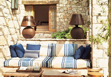 Na tarasie kanapa i niskie stolik. Kamień i drewno w jednym domu