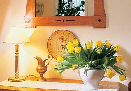 Nad komodą wisi lustro w zdobionej ramie.