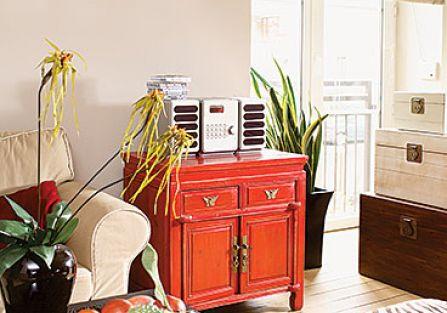 Ozdobą salonu jest czerwona szafka, na której stoi sprzęt rtv.