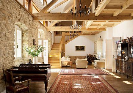 Olbrzymi salon z wysokim sufitem i drewnianymi belkami.