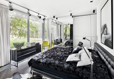Sypialnia z panoramicznym oknem i dizajnerskimi smaczkami: stojace lampy Tolomeo (marki Artemide), czy poduszki z