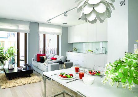 Szafki kuchenne zrobione na zamówienie z lakierowanego MDF-u. Sofa marki Dublo, dywan, szare poduchy i koc - Belbazaar.