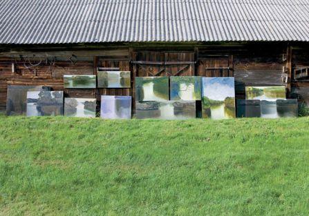 W ładne dni malarz wystawia obrazy przed oborę.