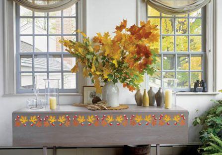 Wielki bukiet jesiennych liści i jesienny wzor wymalowany na stole.