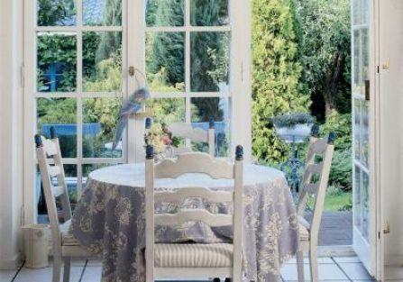 Wokół okrągłego stołu stoją drewniane krzesła.