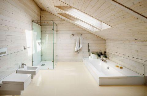 Do subtelnej łazienki z wanną wpuszczona w podłogę pasuje ceramika marki Duravit i prosty przycisk Geberitu.