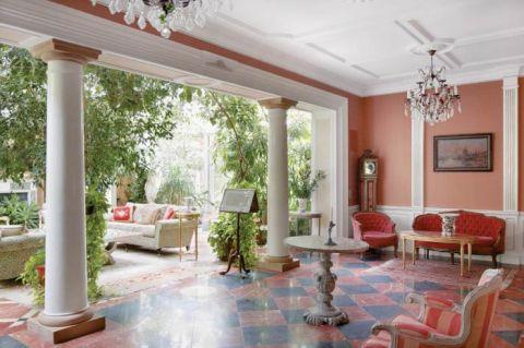 Mały i ciemny salon został powiększony o ogród zimowy. Klasyczny styl podkreślają kopie antycznych rzeźb: