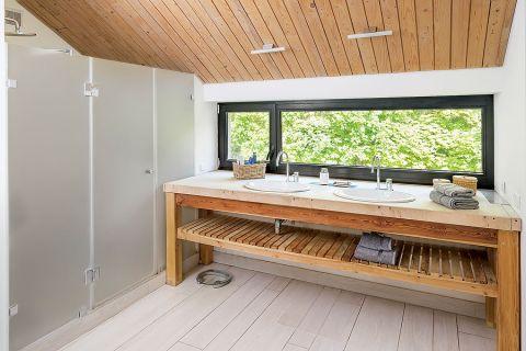 Łazienka w drewnie. Umywalki umiejscowiono pod długim oknem.