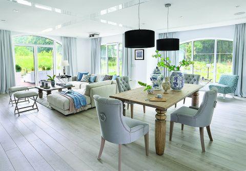 Do dużego masywnego stołu od firmy Jadik pasują fotele ze srebrnymi uchwytami z Decolor i kobaltowe wazony od Casa Mia.
