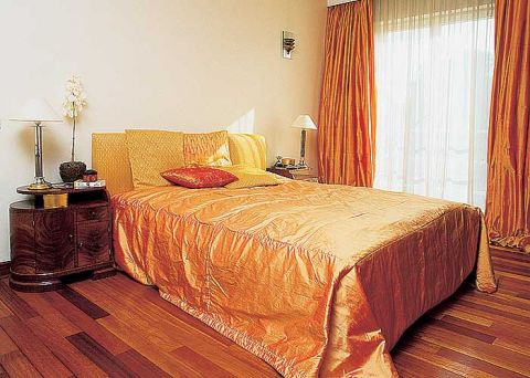 Cieply pomarańcz kapy na łóżku i zasłon ładnie harmonizuje z podłogą.