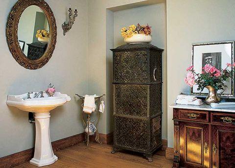 Obok zabytkowego kaflowego pieca współczesna umywalka w klasycznych kształtach.