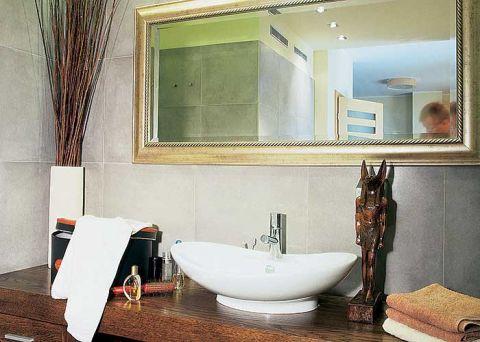 Solidny drewniany blat, ozdobna umywalka i złocona rama lustra kontrastują z surowością przypominającego beton gresu.