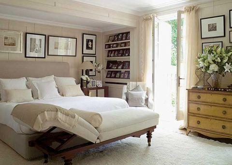 W jasnej sypialni równe rzędy ramek wprowadzają wrażenie porządku.