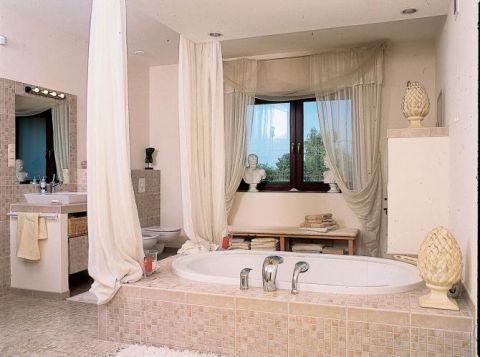 Ta łazienka wygląda jak salon. Wannę otaczają woale, które udają kolumny.