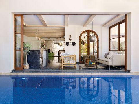 Większość drzwi na parterze rozsuwa się, tak jak te w jadalni. Wystarczą dwa kroki, by urządzić sjestę na basenie.