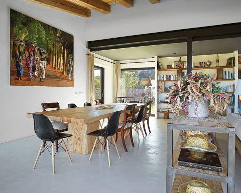 Przy dużym drewnianym stole postawiono krzesła w różnych stylach: nowoczesne i artdecowskie.
