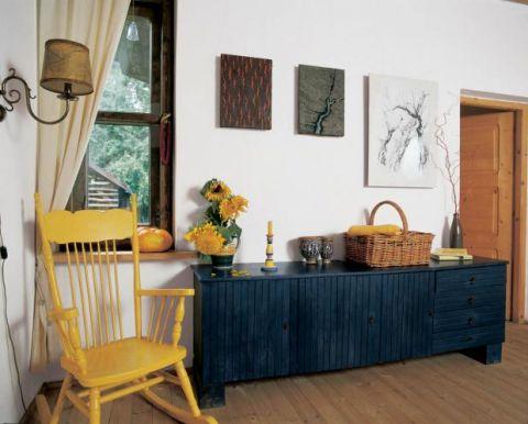 Żółty fotel i niska szafka w ciemnym morskim kolorze.