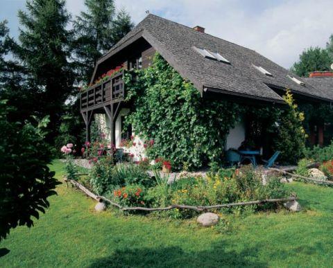 Dom otacza piękny ogródek. Powietrze, drewno i obrazy