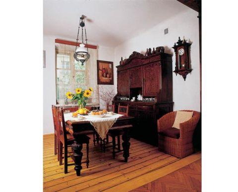 W jadalni stoi kredens, stół i krzesła.
