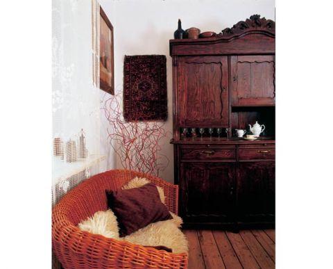 Wiklinowa kanapa świetnie się komponuje ze starym kredensem.