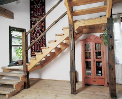 Pod drewnianymi schodami stoi witryna.