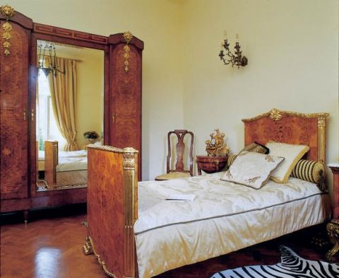 Intarsjowana wieloma gatunkami drewna ogromna szafa z lustrem i empirowe łoże z ozdobione czeczotem i złoceniami.