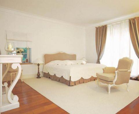 Obok łóżka stoi wygodny fotel. Prostota i naturalność