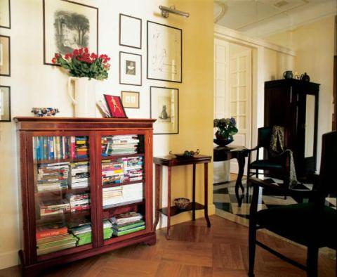 Obok wypełnionej książkami witryny stoi konsola.