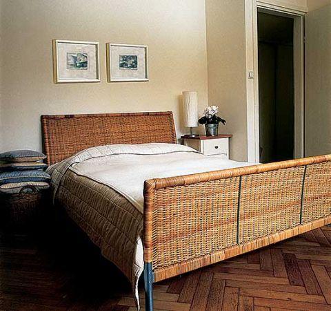 Łóżko ma wiklinową ramę. Różne odcienie bieli