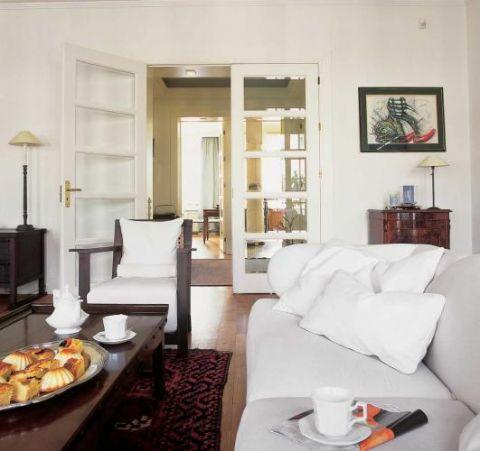 Białe obicia kanapy i foteli kontrastują z ciemnym drewnem.