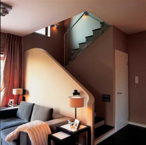 Po obu stronach kanapy stoją lampki.