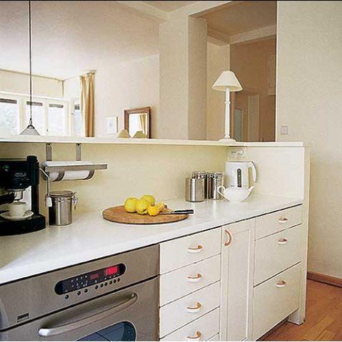 W kuchni znajdziemy białe szafki, których uchwyty akcentuje złota farba.