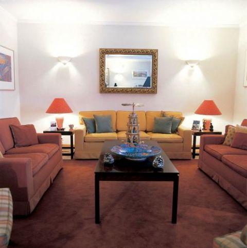 W salonie goście mogą rozsiąść się na kanapach i fotelach w kolorach żółci, ochry i palonej czerwieni.