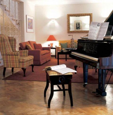 Ceglastoczerwony dywan i abażury lampek dodają wnętrzu przytulności.