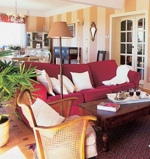 W salonie stoi duża miękka kanapa. Przytulne wnętrze domu w stylu rystykalnym
