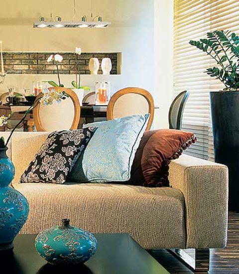 Kolorowe, wzorzyste poduszki kontrastują z surowym ksztaltem i obiciem kanapy.