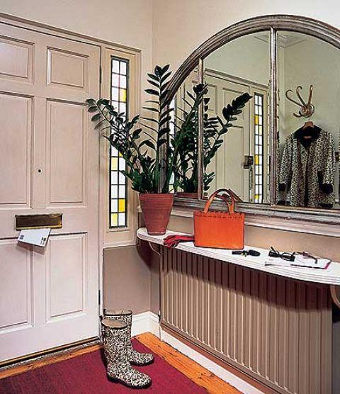 Przy drzwiach wisi lustro w srebrnej ramie.