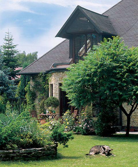 Kamienny dom otacza piękny ogród. Pejzaż wymyślony przy sztalugach