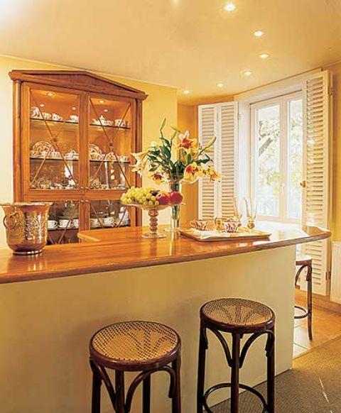 Drogę do kuchni ukrytej dyskretnie za załamaniem muru wskazuje elegancka witryna ze starą porcelaną.
