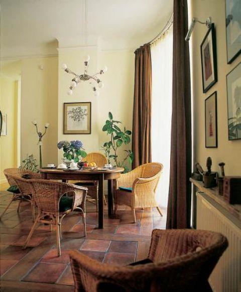 Przy kuchennym stole wiklinowe krzesła.