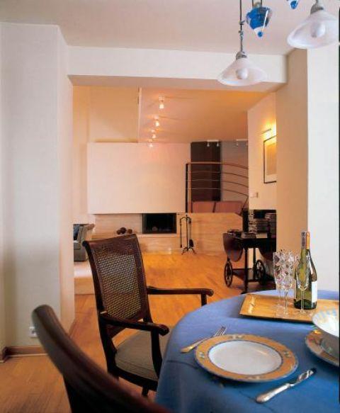 W jadalni owalny stół i zdobione krzesła.