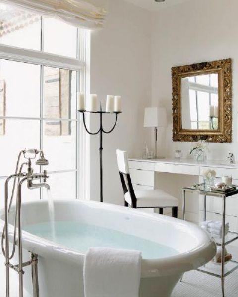 Nad nowoczesną toaletką wisi lustro w zdobionej ramie.