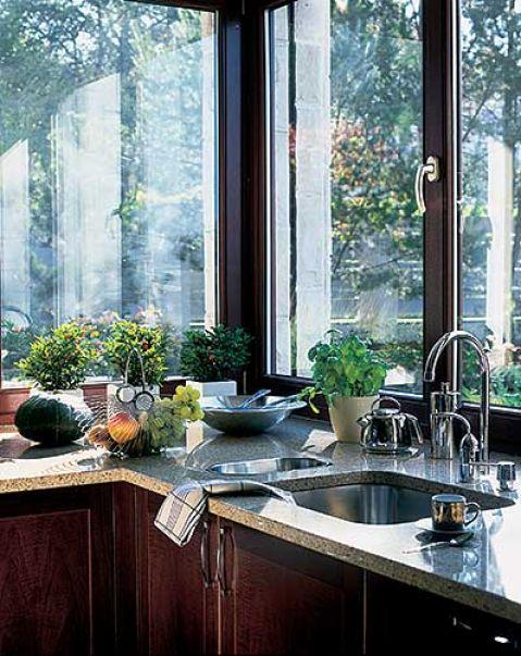 Kuchnia z dużym narożnym oknem kuszącym widokiem.