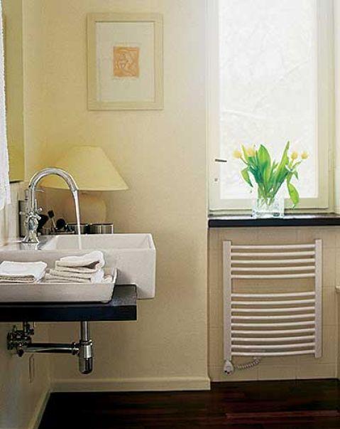 W jasnej łazience akcentem są ciemne blaty.