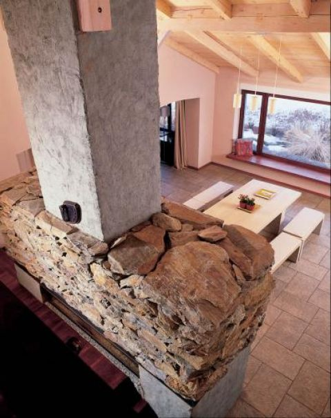 Chropowatość kamienia i nierówna faktura tynków sprawiają, że wnętrze, choć nowoczesne, ma duszę.