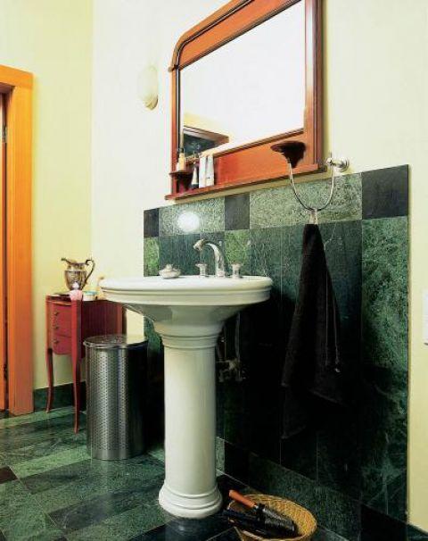 Nad umywalką wisi lustro w drewnianej ramie.